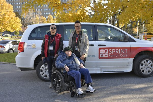 client in wheelchair and 2 staff in front of wheelchair accessible van