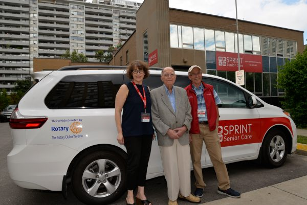 3 standing in front of Rotary Club Donated Van