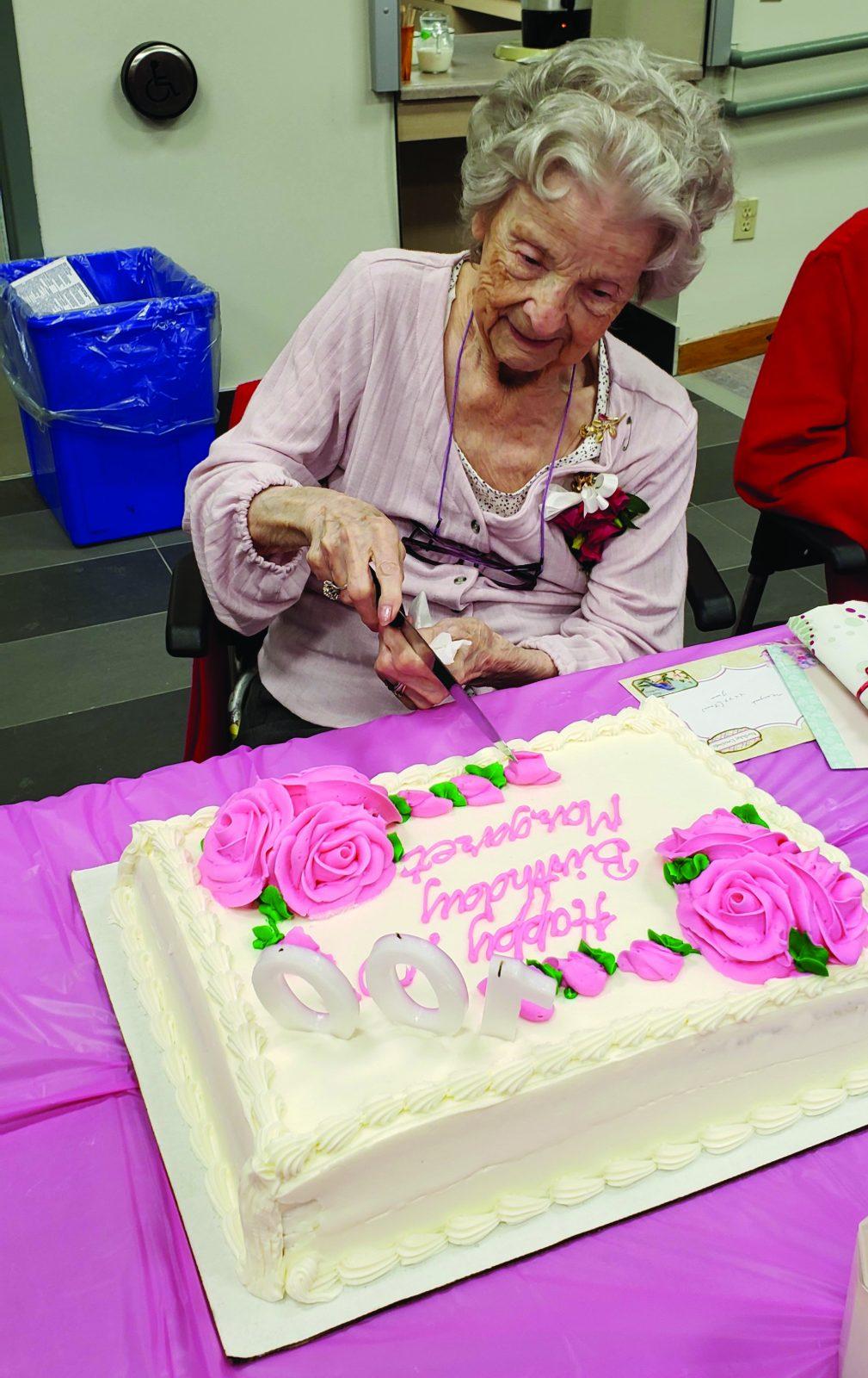 Woman cuts 100th birthday cake