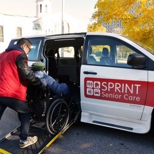 Senior in wheelchair is pushed into SPRINT Senior Care van by man in red vest.